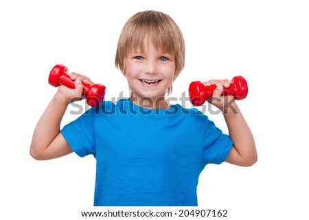 Little strong man. Cheerful little boy looking at camera and smiling while exercising with dumbbells and standing isolated on white - stock photo