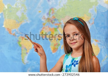 Little student girl pointing to blurry world map with pencil - copy space - stock photo