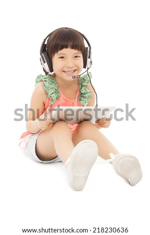 little student girl sitting and holding a tablet with earphone. isolated on white background - stock photo