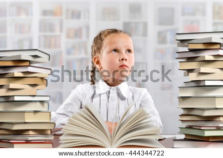 Little student girl with books at school library. Education concept