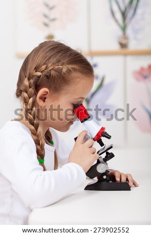 Little student study plants in biology science class - looking at samples on microscope - stock photo