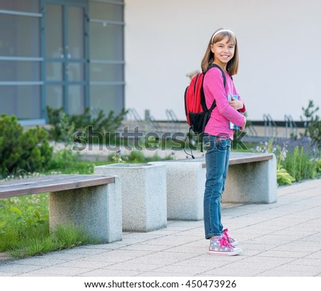 Little students with books - full length outdoor portrait. Beginning of class after vacation. Back to school concept. - stock photo