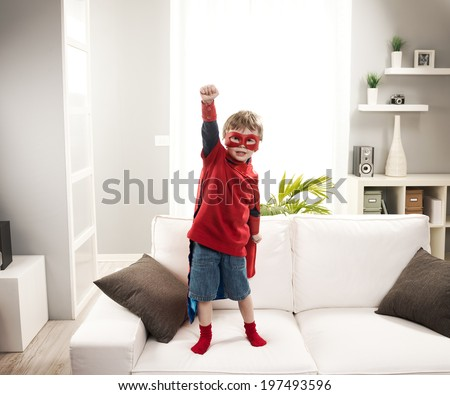 Little superhero boy standing on sofa and posing like a real hero. - stock photo