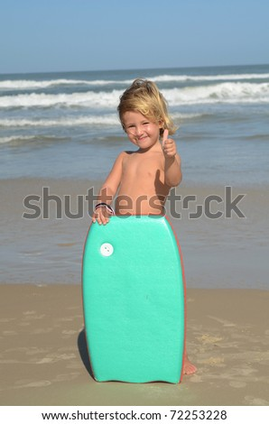 little surfer child with surf board at beach