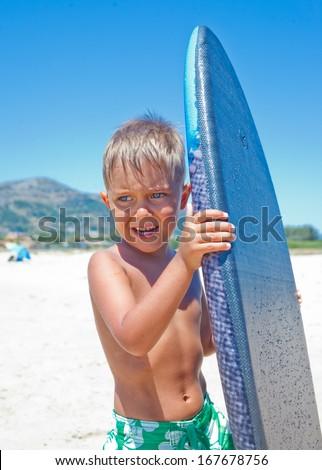 Little surfer. Portrait of cute boy with surfboard standing near ocean. - stock photo