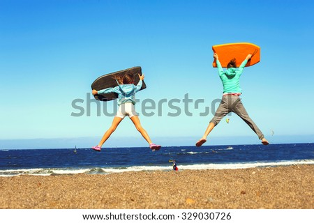 Little surfers. Two jumping kids excitement on windy beach of Atlantic ocean. Canary islands, Tenerife, Spain. Summertime vibrant outdoors horizontal image. - stock photo