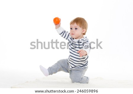 Little sweet boy plays with small orange ball on a white background. - stock photo