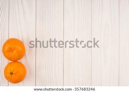 little tangerines on white wood table - stock photo
