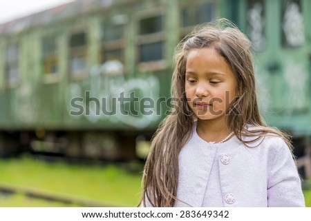 little thai girl in front of train carriage. shallow depth of field. this image looks great in black & white, or sepia. - stock photo