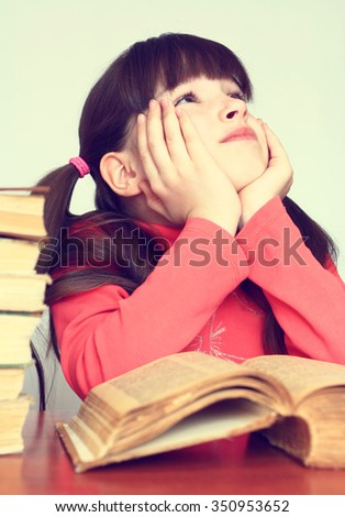 Little thoughtful girl on a pile of old books. - stock photo