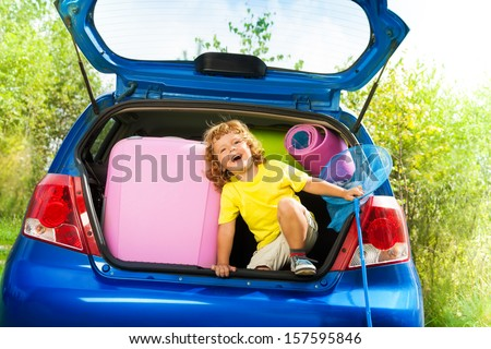 Little three years old boy sitting in the car trunk with bags, net-scoop and mate for the trip in the car - stock photo