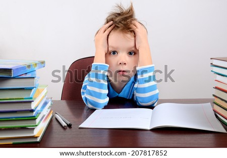 little tired boy sitting at a desk and holding hands to head horizontal - stock photo