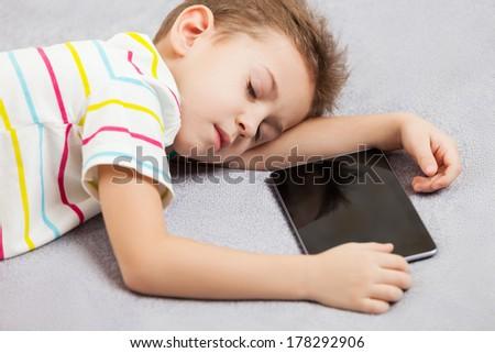Little tired sleeping child boy hand holding digital tablet computer - stock photo