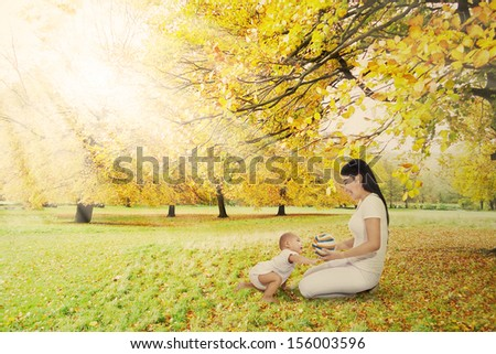 Little toddler and young mother playing with ball in the autumn park - stock photo