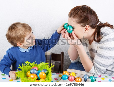 Little toddler boy and his mother having fun with Easter egg hunt, traditional action in Germany for Eastern holiday - stock photo