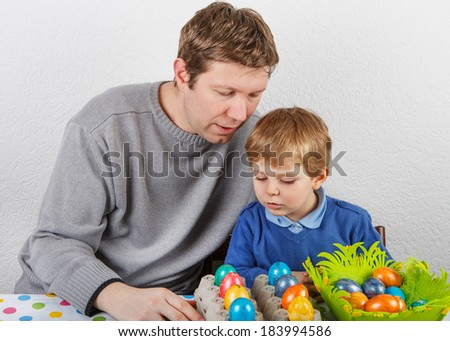 Little toddler boy and his mother having fun with preparing eggs for Easter egg hunt, traditional action in Germany for Eastern holiday, indoors - stock photo