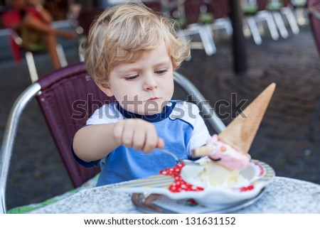 Little toddler boy eating ice cream in summer city cafe