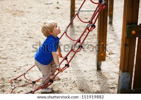 Little toddler boy having fun on playground in summer