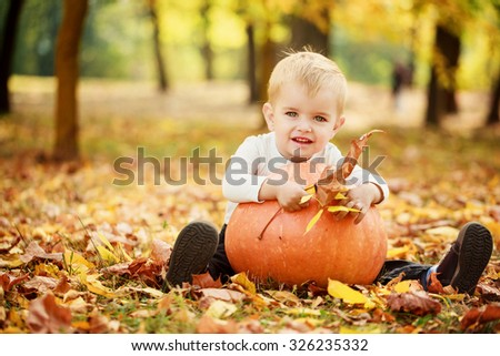 Little toddler boy having fun with orange pumpkin in autumn park.