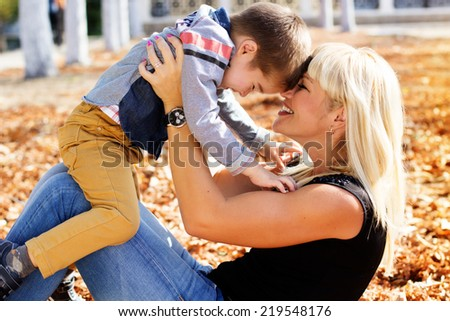 Little toddler boy in autumn park with his mother - stock photo