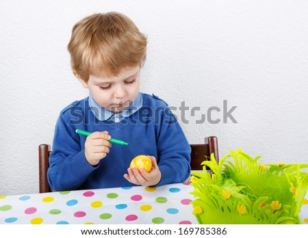 Little toddler boy painting colorful Easter egg for hunt, traditional action in Germany for Eastern holiday - stock photo