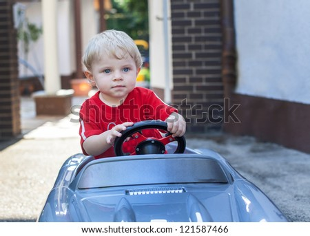 Little toddler boy playing with big toy car in summer garden