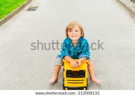 Little toddler boy playing with big toy car, outdoors