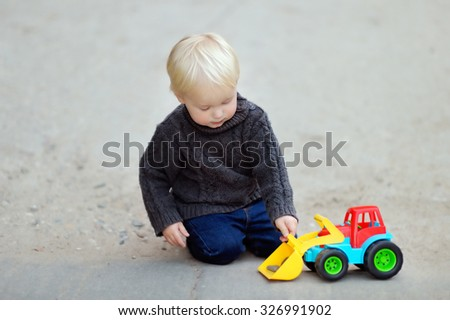 Little toddler boy playing with bright car toy