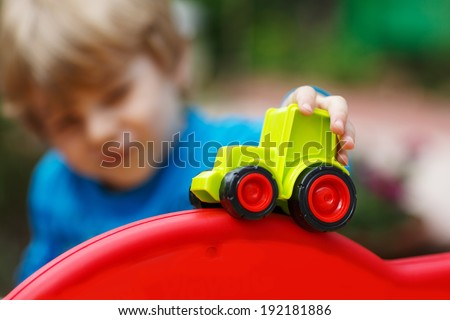 Little toddler boy playing with car toy. Selective focus on hand of toddler and toy - stock photo