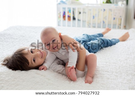 Little toddler boy, playing with his little brother at home in bedroom