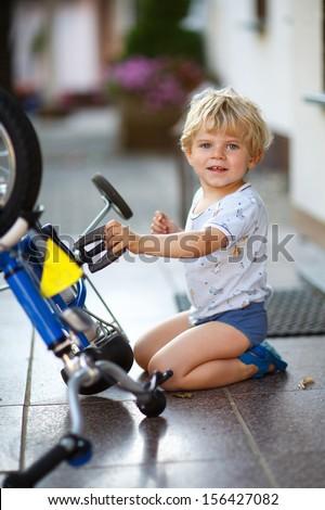 Little toddler boy repairing his first bike - stock photo
