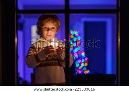 Little toddler boy standing by window at Christmas time and holding candle. With colorful lights from Christmas tree on background, selective focus. - stock photo