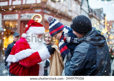 Little toddler boy with father on Christmas market. Funny happy kid taking gift from bag of Santa Claus. holidays, christmas, childhood and people concept - stock photo