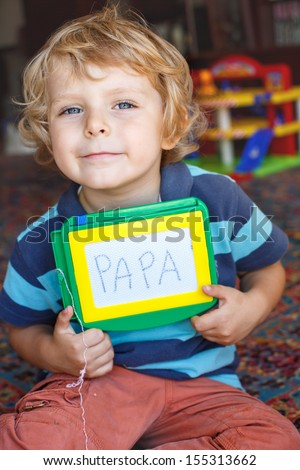 Little toddler boy with painting board writes his first word papa - stock photo