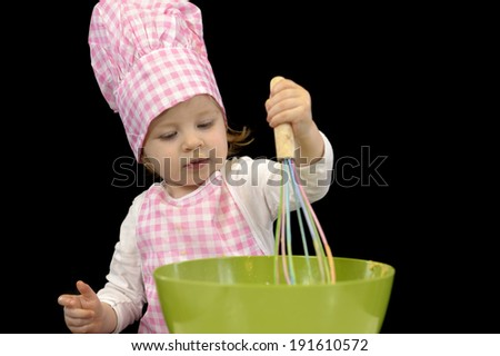 little toddler cooking pastry, black background - stock photo