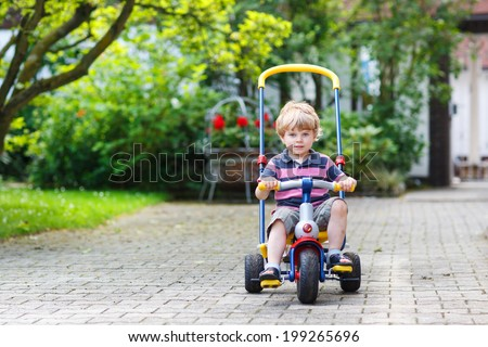 Little toddler driving tricycle or bicycle in home garden - stock photo