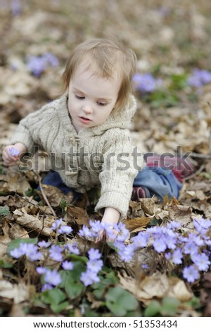 Little toddler girl and the first flowers of spring - stock photo