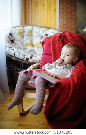 Little toddler girl eating chocolate and reading a book