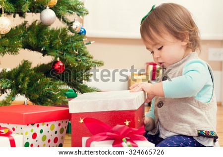 Little toddler girl gifts presents under her Christmas tree - stock photo
