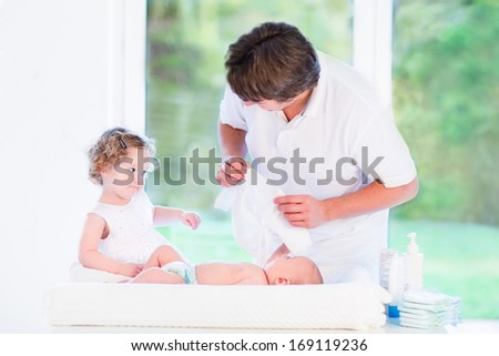 Little toddler girl helping her father to choose an outfit for her newborn baby brother standing in a room with white furniture and a big garden view window on a sunny morning - stock photo