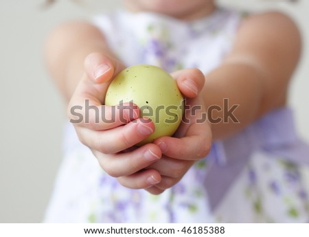 Little toddler girl holding a hand painted egg in her hands - stock photo