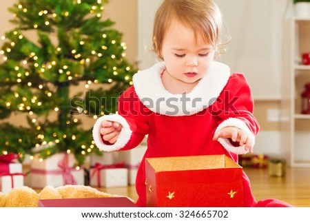 Little toddler girl in red winter dress opening Christmas presents - stock photo