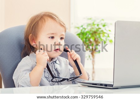 Little toddler girl putting on big glasses while using her laptop - stock photo