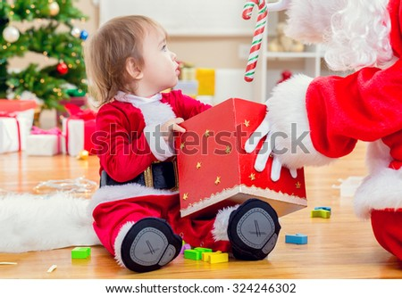 Little toddler girl receiving a gift from Santa Claus by the Christmas tree - stock photo