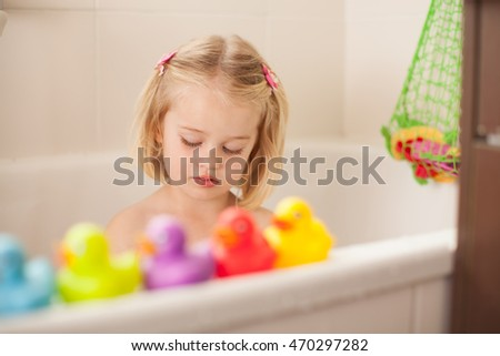 Little toddler having a bath with her duckies
