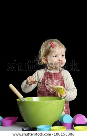 little toddler making deserts, on black background