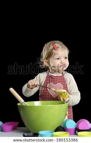 little toddler making deserts, on black background - stock photo