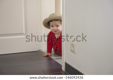 little toddler playing hide and seek , inside - stock photo