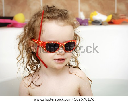 Little toddler playing in the bath with sunglasses - stock photo