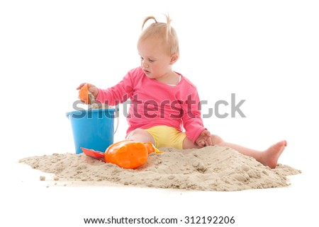 Little toddler playing in the sand isolated over white background - stock photo